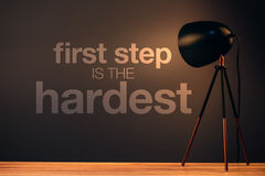 First step is the hardest. Motivational message on office wall illuminated by the desk lamp Royalty Free Stock Photos