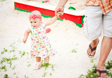 First steps. Baby girl first steps holding her father hand Royalty Free Stock Photos