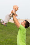 First Steps baby boy with father in the park. Around a lot of green grass and trees in the summer. Stock Image