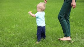 First steps baby boy with help mother. Slow motion stock footage