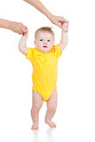 First steps of baby boy with help of mothers hands. First steps of baby with help of mothers hands royalty free stock photography