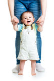 First steps of baby boy with mother support. First steps of baby boy with help of mothers hands Royalty Free Stock Photography
