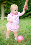 First steps of a baby girl. Baby girl standing in a park holding father's hand royalty free stock images