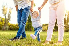 The first steps of the baby. A happy family. The first steps of the baby. Parents are teaching their child to walk. A happy family stock photos