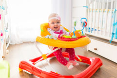 First steps in a baby walker Stock Photos