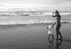 First Steps on the Beach. Baby girl holds her moms hand as she takes her first steps on the beach Stock Photos