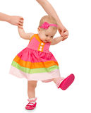First steps of a beautiful cute baby girl with  hand of mother i Stock Photos