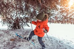 The first steps of a boy child 3-5 years old on children`s skiing with sticks. In park in winter. The concept of sports royalty free stock images