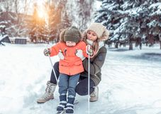 The first steps of a boy`s child on children`s skiing with sticks. Play and have fun ride in park in winter. Mom keeps royalty free stock photography