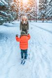 The first steps of a boy`s child on children`s skiing with sticks. Play and have fun ride in the park in winter. Mom stock image