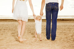 First steps of the kid. Happy family is helping baby takes first Stock Photos