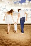 First steps of the kid. Happy family is helping baby takes first. Steps on the beach royalty free stock images