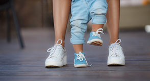 The first steps of the kid. Mom in white sneakers with a young son, dressed in blue pants and blue shoes, a warm summer day and learn to walk in the street, the Royalty Free Stock Images