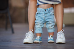 The first steps of the kid. Mom in white sneakers with a young son, dressed in blue pants and blue shoes, a warm summer day and learn to walk in the street, the Stock Images