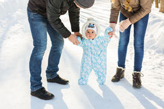 First steps of little baby boy in winter park Stock Photos