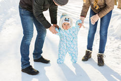 First steps. Little baby learning to walk. Mother and father with toddler boy at the winter park Royalty Free Stock Photography