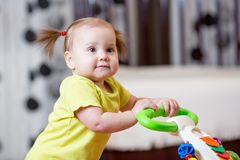 First steps of little girl in baby walker Royalty Free Stock Images