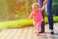 First steps of little girl with mother outdoors Stock Photo