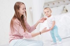 First step. happy mother and walking infant baby Royalty Free Stock Images
