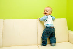 First steps on sofa. Baby first steps on sofa. Baby looks behind and smiles stock photos
