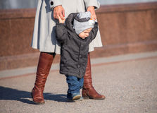 First steps of toddler. With his mother outdoors Stock Photography