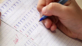 First steps in writing: little boy writes digits in diagonal lined notebook stock footage
