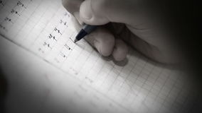 First steps in writing: little pupil write digits in square grid notebook stock video footage