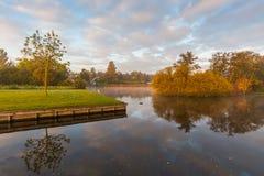 First sun illuminates the autumn leaves above misty lake. Royalty Free Stock Image
