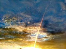 First Sun Ray Flash. In Summer Sky  Gold Sun Ray Penetrate Blue Rains Clouds and rise to Space Royalty Free Stock Images