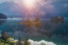 First sun rays on the mountain lake Eibsee in Bavarian Alps. sunrise over mountains and small island with reflection stock photos