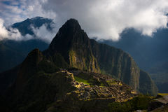First sunlight on Machu Picchu from opening clouds Stock Photos