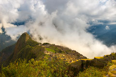 First sunlight on Machu Picchu from opening clouds Royalty Free Stock Images