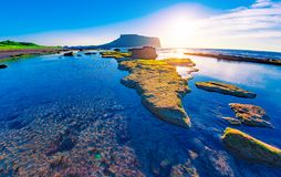 Free First Sunrays At Sunrise At Ilchulbong Volcano Crater With View Over Ocean And Green Moss Stones , Jeju Island, South Korea Royalty Free Stock Image - 157833406