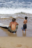 First Surfing Lesson. Young boy and his dad going on the boy's first surfing adventure royalty free stock image
