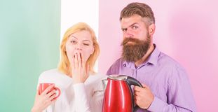 First thing they do every morning prepare hot drink. Get energy charge favourite hot drink. Enjoying morning coffee. Man. With electric teapot and women with royalty free stock photos