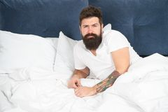 First thing you do after awakening. Man bearded hipster sleepy face relax in bed. Early morning hours. Relax and sleep stock photography