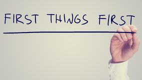 First Things First. Retro effect concept - First Things First - with a man writing the words on a virtual interface with a marker pen over white with copyspace Royalty Free Stock Images