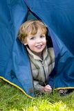 First Time Camping. A young boy emerges from a tent on a camping trip stock photos