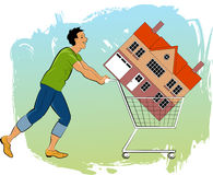 First time homeowner. Young man pushing a shopping cart with a house in it Royalty Free Stock Image