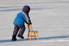 First Time Skater. A young boy uses a chair as support as he skates for the first time royalty free stock images