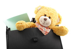 First time to school set. Teddy bear and copybook in a briefcase isolated over white Stock Images