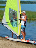 The first windsurfing lesson. The instructor is explaining how to manage the sail. Sport activity and rest. Plescheevo lake near Pereyaslavl-Zalessky, Russia Royalty Free Stock Photos