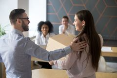 First working day concept, boss welcoming new employee in office. First working day in office concept, friendly male boss welcoming new female employee holding Royalty Free Stock Photography