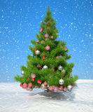 Firtree with Xmas decoration during snowfall. Over blue sky. Useful for New Year postcards Stock Photography