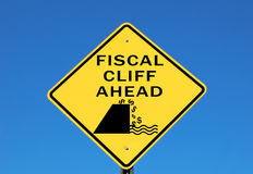 Fiscal cliff. Warning sign with dollar signs falling off the cliff Royalty Free Stock Photo