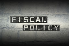 Fiscal policy GR. Fiscal policy stencil print on the grunge white brick wall Royalty Free Stock Photo