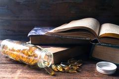 Fischöl und alte Bücher auf dem hölzernen Hintergrund Stockbilder