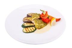 Fisch-Steak mit gegrilltem Gemüse, weißer Soße und Zitrone Stockfotografie