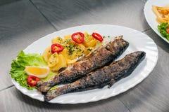 Fische auf Platte mit Kartoffel Stockbilder