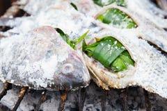 Fische bedecken durch das gegrillte Salz Stockfotos